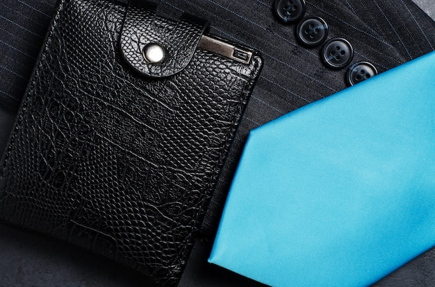Blue men's necktie, jacket sleeve, and black wallet. concept image of a successful business man