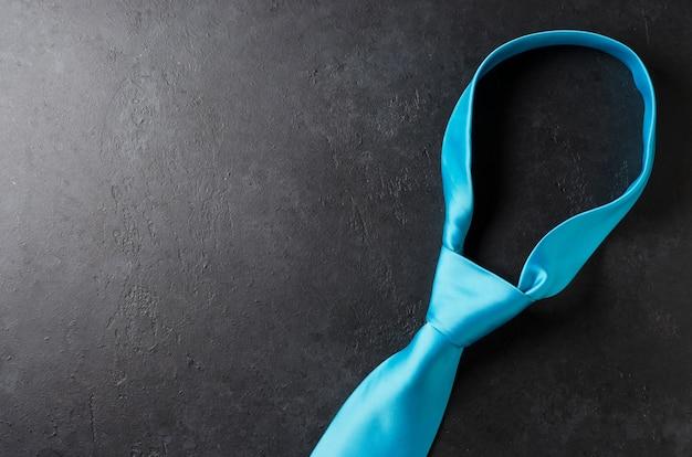 Blue men's tie on a black concrete table