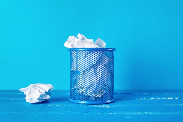 Blue metal bucket filled with crumpled white paper