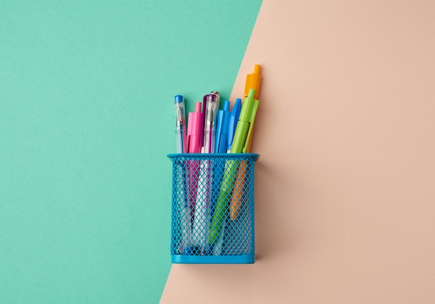 Blue metal container for stationery, inside multi-colored plastic pens