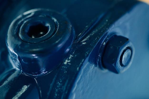 Синяя металлическая шероховатая поверхность детали с болтами и гайками. синяя окраска автозапчастей