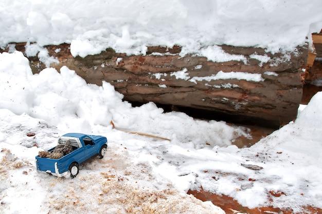 제재소에 있는 파란색 금속 장난감 픽업 트럭 눈 더미와 톱밥에 갇힌 전나무 원뿔을 뒤쪽에 운반