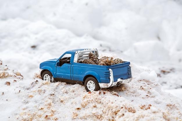 제재소의 파란색 금속 장난감 픽업 트럭 눈 더미와 톱밥에 갇힌 전나무 콘을 운반