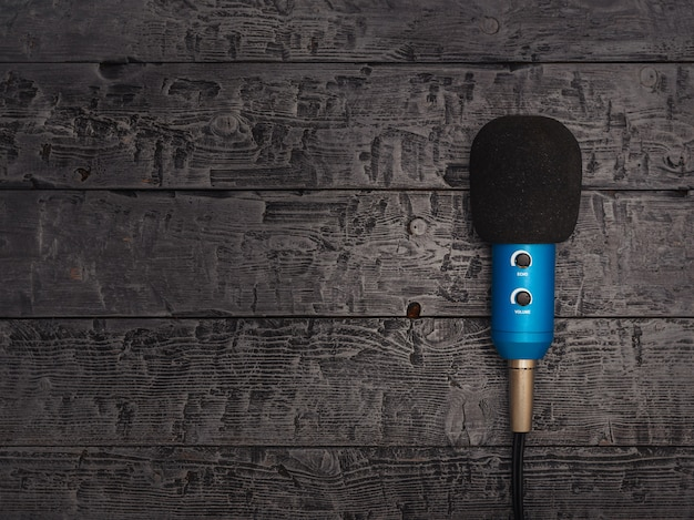 Blue microphone with wire on black wooden table.