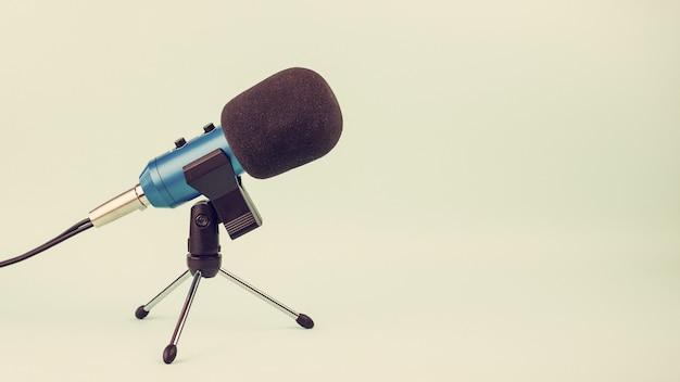 ビンテージスタイルのスタンドにワイヤーと青いマイク。スタジオやコンサートのための機器。
