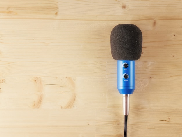 The blue microphone with the wire on a wooden background. equipment for studio and concerts. flat lay.