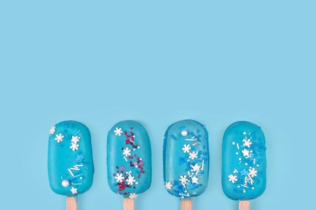 青い背景に青いミントアイスクリームアイスキャンディー。スティックにおいしくてさわやかなアイスクリーム。最小限の夏のコンセプト。フラットレイ、テキスト用の無料コピースペース