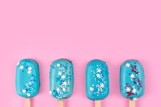 パステルピンクの背景にブルーミントアイスクリームアイスキャンディー。スティックにおいしくてさわやかなアイスクリーム。最小限の夏のコンセプト。フラットレイ、テキスト用の無料コピースペース