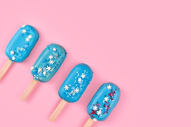 Blue mint ice cream popsicles on pastel pink background. tasty and refreshing icecream on sticks. minimal summer concept. flat lay, free copyspace for text