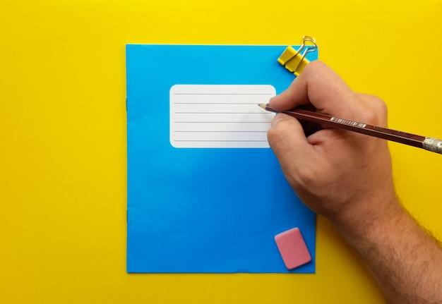 黄色の背景に学校の科目、消しゴム、鉛筆、ペーパークリップ用の青いモックアップノートと教科書のお尻。フラットレイ、コピースペース、上面図、テキストの場所。