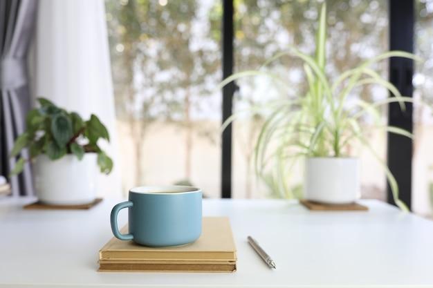 植木鉢とキーボードが付いている白いテーブルの上の青い現代マットコーヒーカップと鉛筆と茶色のノートブック