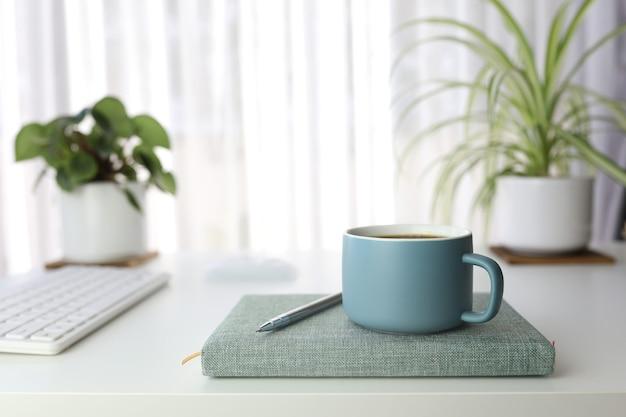 植木鉢とキーボードが付いている白いテーブルの上の青い現代マットコーヒーカップと鉛筆と緑のノートブック
