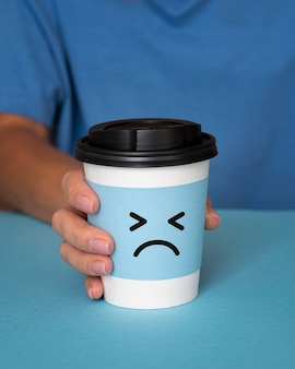 Concetto di lunedì blu con la faccia triste sulla tazza