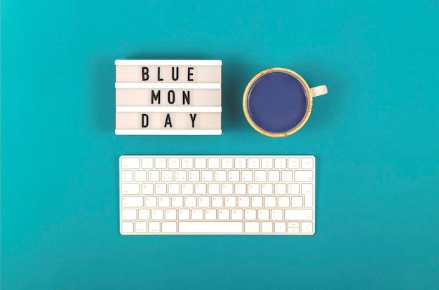 키보드와 파란색 배경에 음료 가운데 파란색 월요일 비문. 우울한 기분 개념