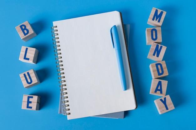 Lunedì blu con blocco note, penna e cubi di legno