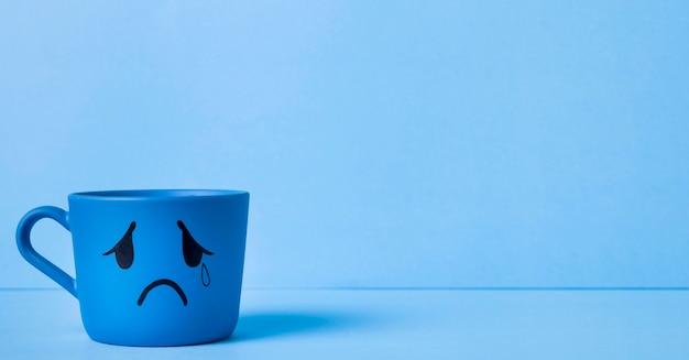 涙のマグカップとコピースペースのある青い月曜日