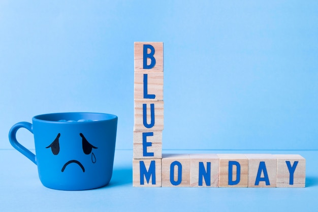 Blue monday with wooden cubes and teary mug
