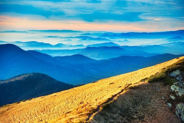 美しい夕日の上の青い山と丘
