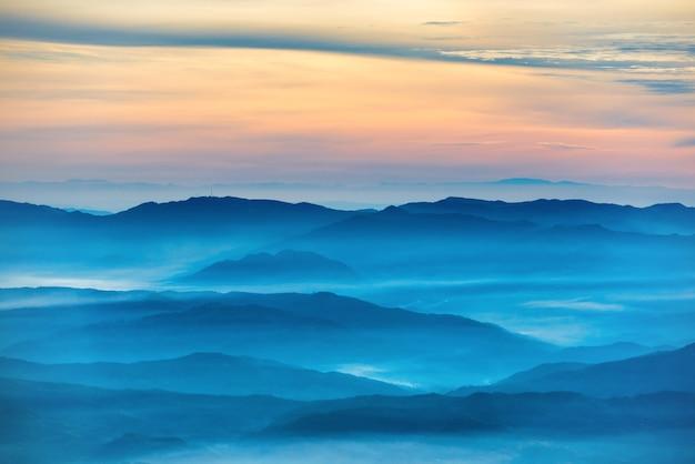 Голубые горы и холмы под красивым оранжевым закатом