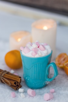 Blue mug of drink with whipped cream and marshmallows