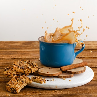 Blue mug with splashing coffee and cookies on wooden background