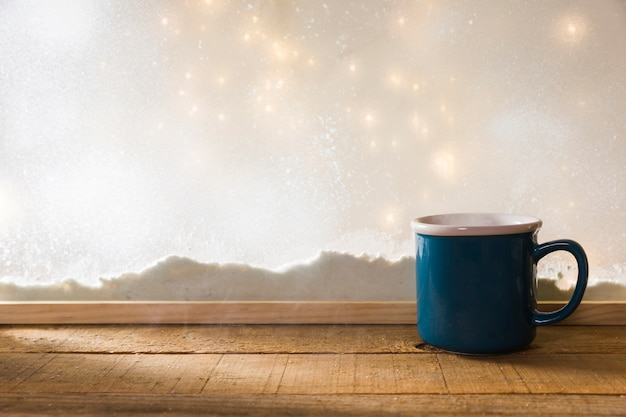 Blue mug on wood table near bank of snow and fairy lights