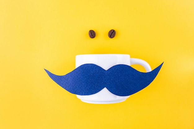 Blue mustache on a coffee mug, next to a coffee grain for movember concept