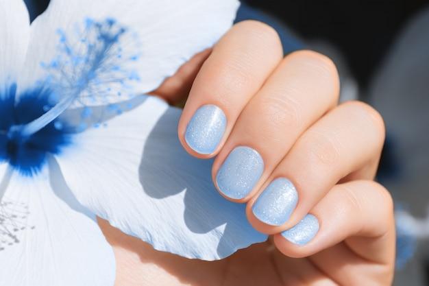 ブルーネイルデザイン。キラキラのマニキュアで女性の手。