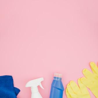 Голубая салфетка; моющее средство и распылитель на розовом фоне