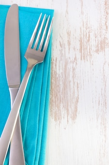 Blue napkin on white with fork and knife