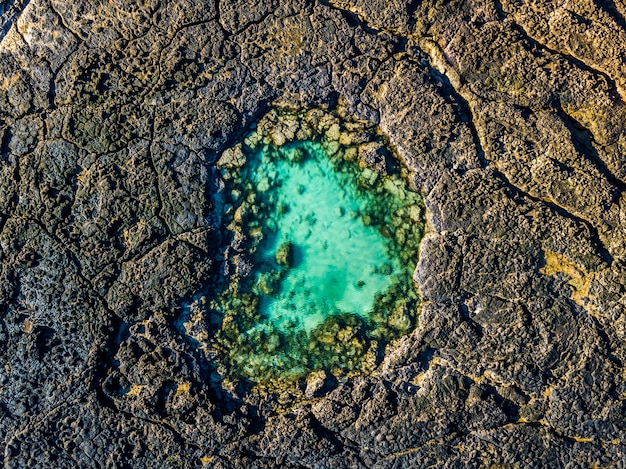 Blue natural swimming pool in the middle of black volcanic rocks - green lagoon ocean water - aerial top view - beauty of planet and earth's day concept - summer holiday vacation destination