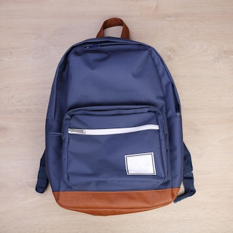 Blue navy backpack on wooden background