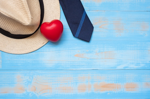 Blue necktie with hat and red heart shape on wooden background