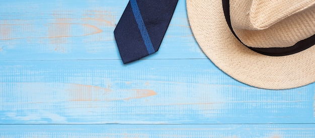 Blue necktie with hat on wooden background with copy space for text