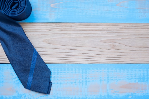 Blue necktie on wooden background with copy space for text