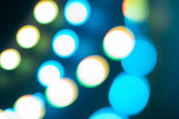 青いネオンのぼやけたライトの抽象化と反射。 80年代の色のお祝いの冬の背景。