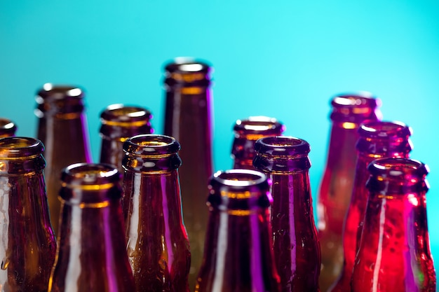 Синий. неоновые цветные пивные бутылки, крупным планом, изолированные на ярком фоне студии. понятие пива, напитков, развлечений и алкоголя. copyspace для рекламы вашего бара, ресторана, пивоварни или магазина.
