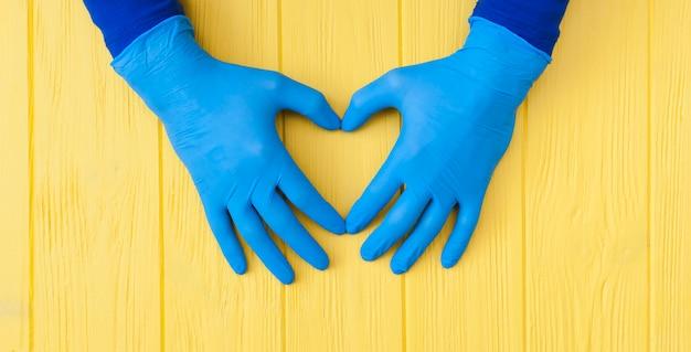 ブルーニトリル手袋。黄色の木製テーブルバナーに青いラテックス手袋でメディックの手