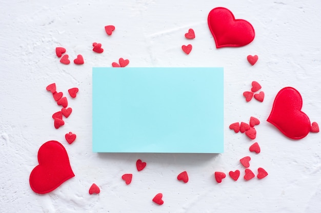 Blue note sheet on a white background and a lot of red hearts confetti. copy space.