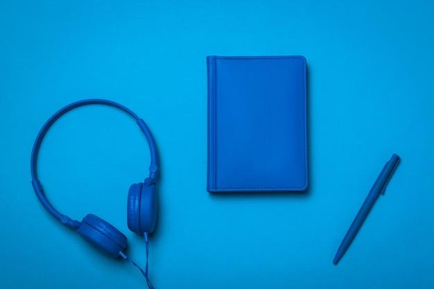 青いノート、ヘッドフォン、青い背景のペン。オフィスアクセサリーのモノクロ画像。