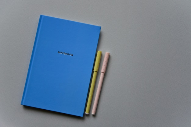 Blue notebook with two pens on a gray paper background. top view. close-up. flat lay.