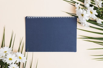 Blue notepad and white flowers