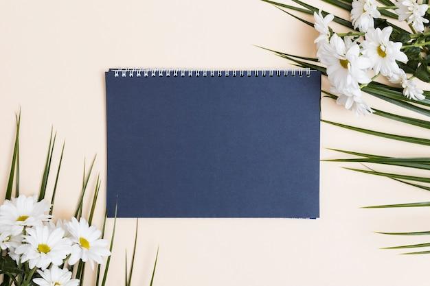 青いメモ帳と白い花