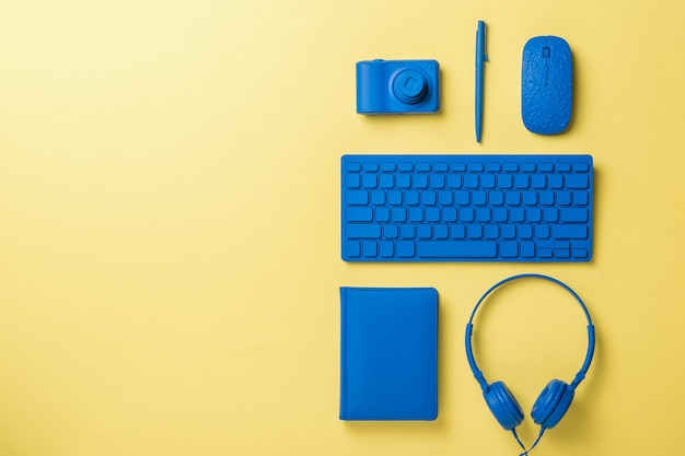 Blue office accessories on a light yellow background. stylish accessories for business and freelancing. flat lay.
