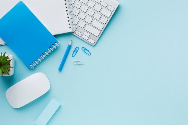 Синие канцелярские принадлежности и клавиатура