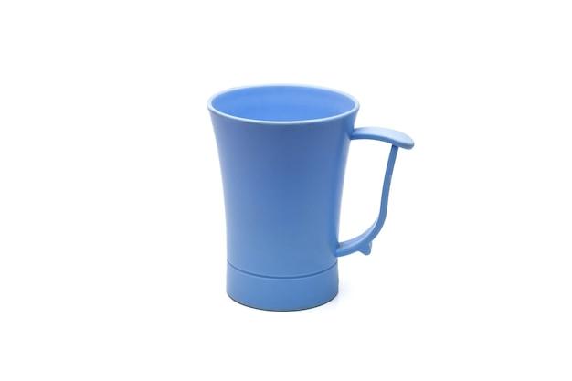青い古いプラスチック製のお茶のマグカップは、孤立した白い背景にクローズアップ