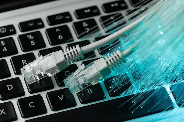 Синее оптоволокно с кабелями ethernet и ноутбуком