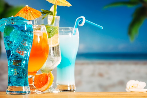 Blue orange drinks with sliced lime mint ice cubes in bright umbrella decorated glasses