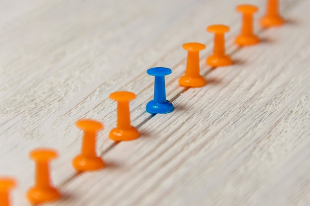 Blue and orange pushpins arrayed in row on white wood
