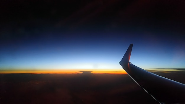 Blue orange sunset from a sky height. airplane wing.